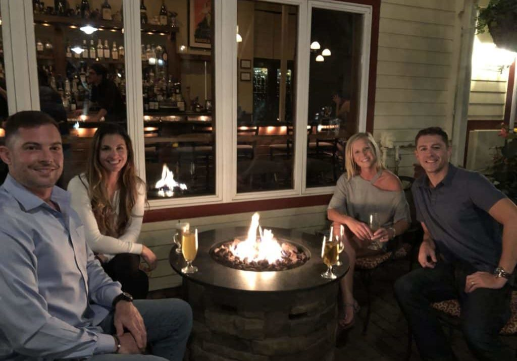 couples drinking by firepit